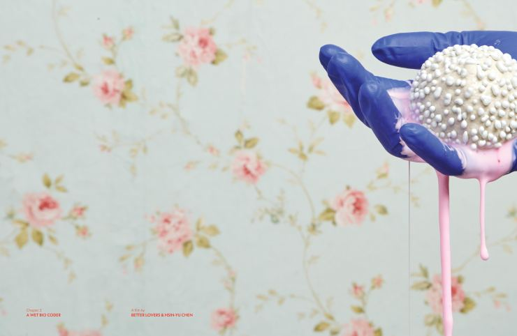 Film still from Chapter 2: A Wet Bio by Coder Better Lovers, Hsin-Yu Chen. A hand wearing a surgical blue glove is holding a white, strangely textured ball dripping with pink slime, on a floral wallpaper background.