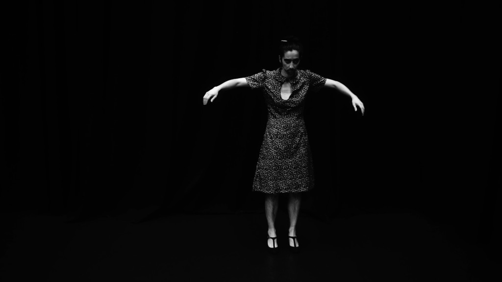 Film still from This dance has no end by Fenia Kotsopoulou. Black and white image of person wearing dress, in motion with arms stretched and pointing downwards.