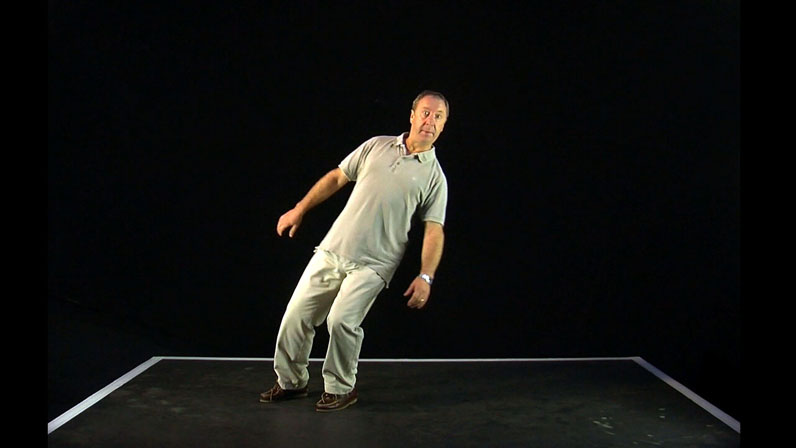 Film still from Gravity Shift by Nic Sandiland & Yael Flexer. A man leans to the right inside a white taped box on the floor of a black room.