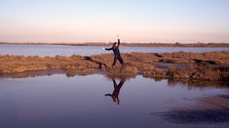 Film still from Intertidal. Barene by Laura Santini. Woman dancing on grassy piece of land, among still reflective water.