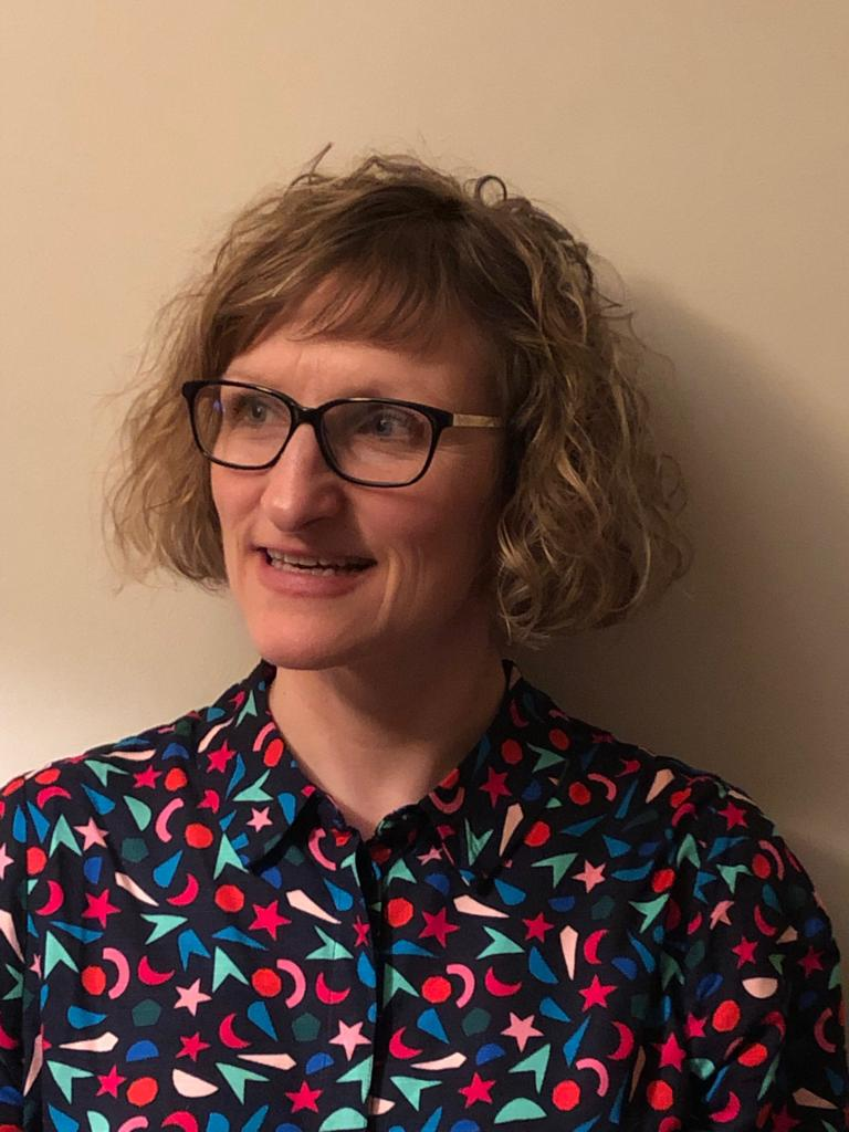 An image of Karen Wood, a white woman with glasses wearing a colourful shirt.