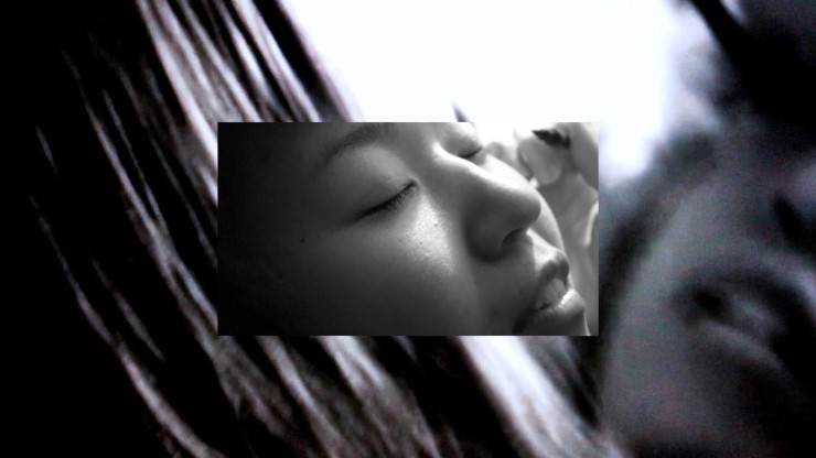 Film still from Lorelei - Persona by Gustavo Gomes. Rectangular image of a woman with eyes closed, layered on a background of black and white light.