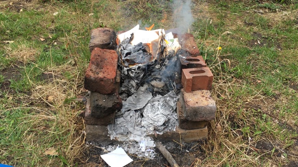 Film still from notes on symptoms by Alice Gale-Feeny. Stacked bricks among grassy landscape, burning papers on fire in the centre.