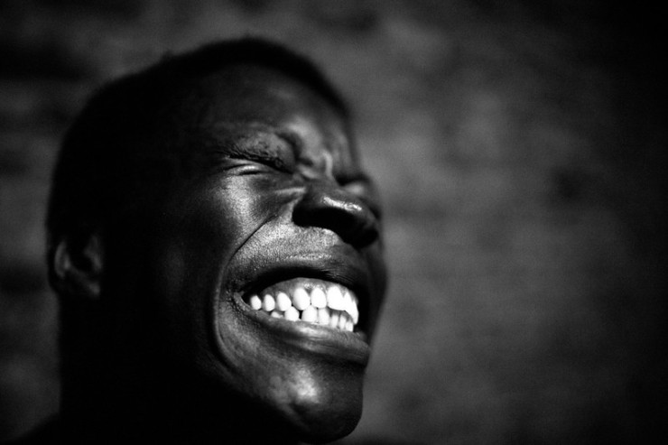 Film still from Observations by David Belotti. Black and white still image of a man, cannot tell if he is smiling or grimacing.