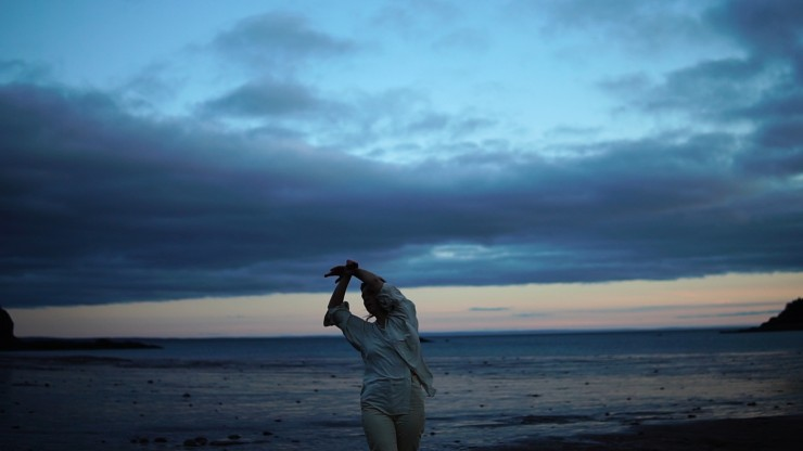 Film still from the moon rises in four parts by Michaela Gerussi & Tracy Valcarel. Person in motion in foreground of seaside landscape at dusk.