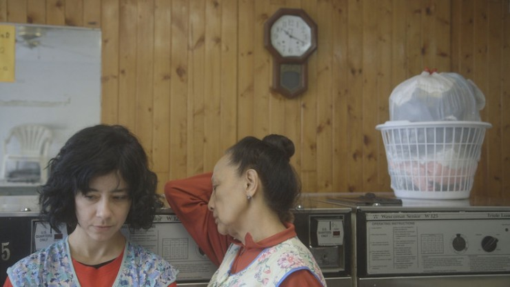 Film still from The Washing Society by Lynne Sachs & Lizzie Olesker. Two women rest in front of large washing machines, there is a clock on the wall and a laundry basket full of washing on top of the washing machines.