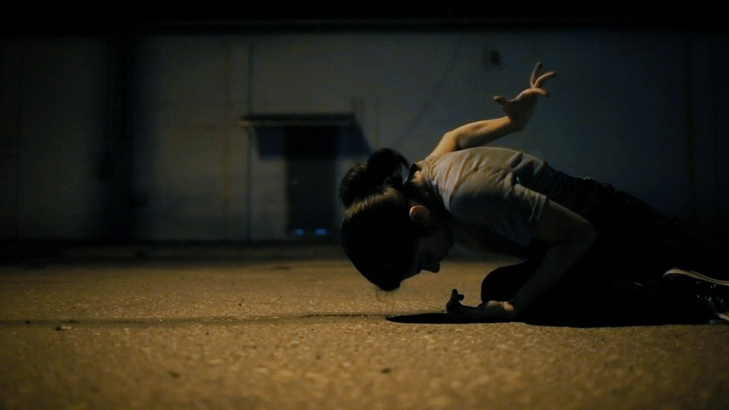 Film still from Unfurling by Alexa Velez. Woman kneeling on concrete ground, performing awkward hand gesture behind her back, in front of industrial looking building.