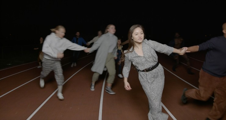 Film still from We Are Ready Now by Jack Thomson. People in motion, holding hands in pairs, on a marked out race track.