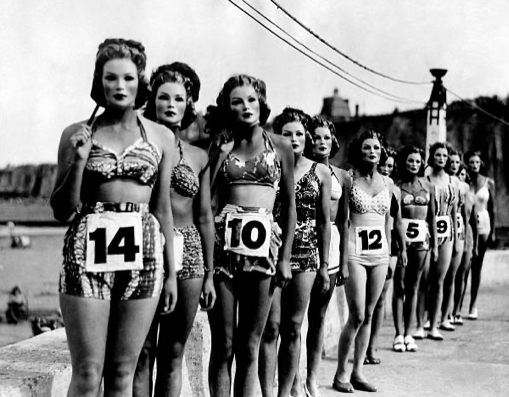 Film still from Between the sea and the land by Adesola Akinleye. Black and white image of women lined up wearing bathing suits on the beach with numbers pinned to their waists.